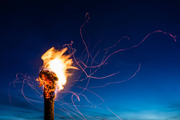 Flaming Torch at Night Flaming wooden torch with flying sparks framed by a deep-blue late evening sky. flaming torch stock pictures, royalty-free photos & images