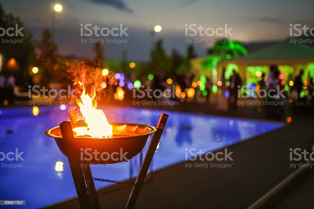 Flaming torch at sunset by the pool stock photo