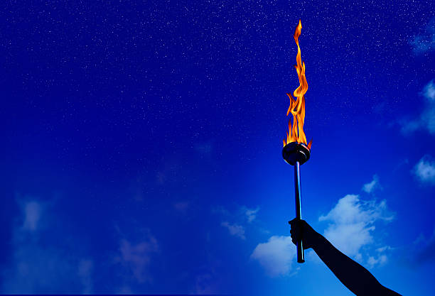 flaming torch of success silhouetted hand holding burning flaming torch over night sky with stars.  flaming torch stock pictures, royalty-free photos & images