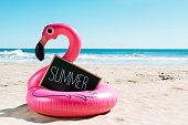 a signboard with the word summer written in it and a swim ring in the shape of a pink flamingo, on the sand of a beach, with the ocean in the background
