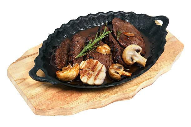 flankensteak gebacken in einem ovalen gusseisen-platte - flank steak marinaden stock-fotos und bilder