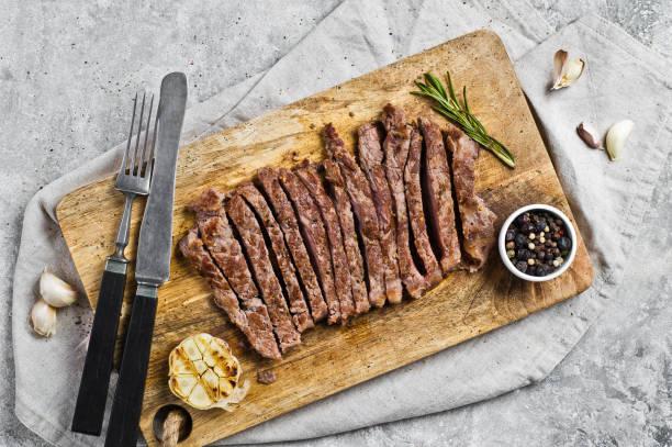 flank-steak auf einem hölzernen hackbrett. grauer hintergrund, obere ansicht, platz für text - flank steak marinaden stock-fotos und bilder