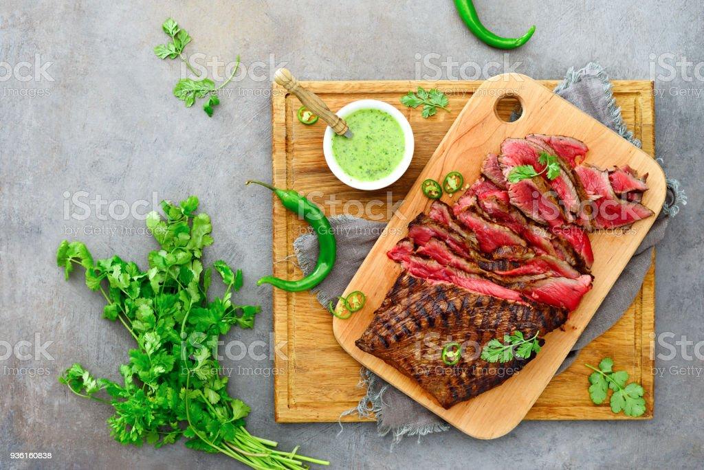 Flank steak on a wooden cutting board stock photo
