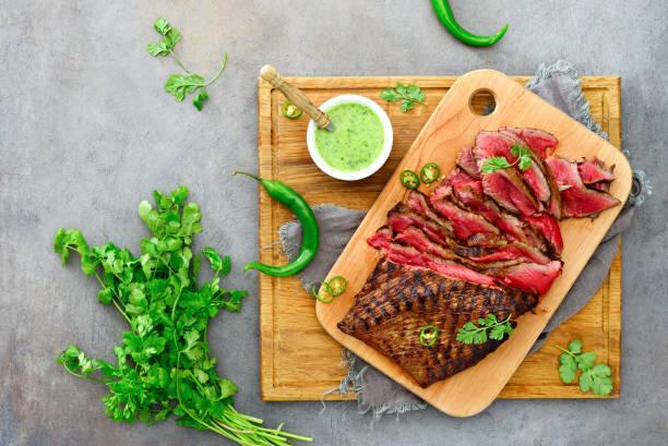 flanke steak auf einem holzbrett - flank steak marinaden stock-fotos und bilder