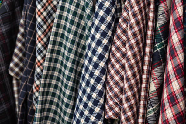 Flannel shirts hanging Details of a check or lumberjack flannel shirts which hang in a row plaid shirt stock pictures, royalty-free photos & images