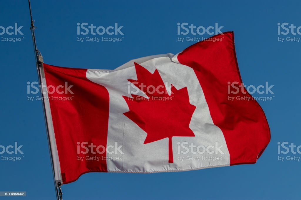Flapping Canadian flag against a blue sky background. stock photo