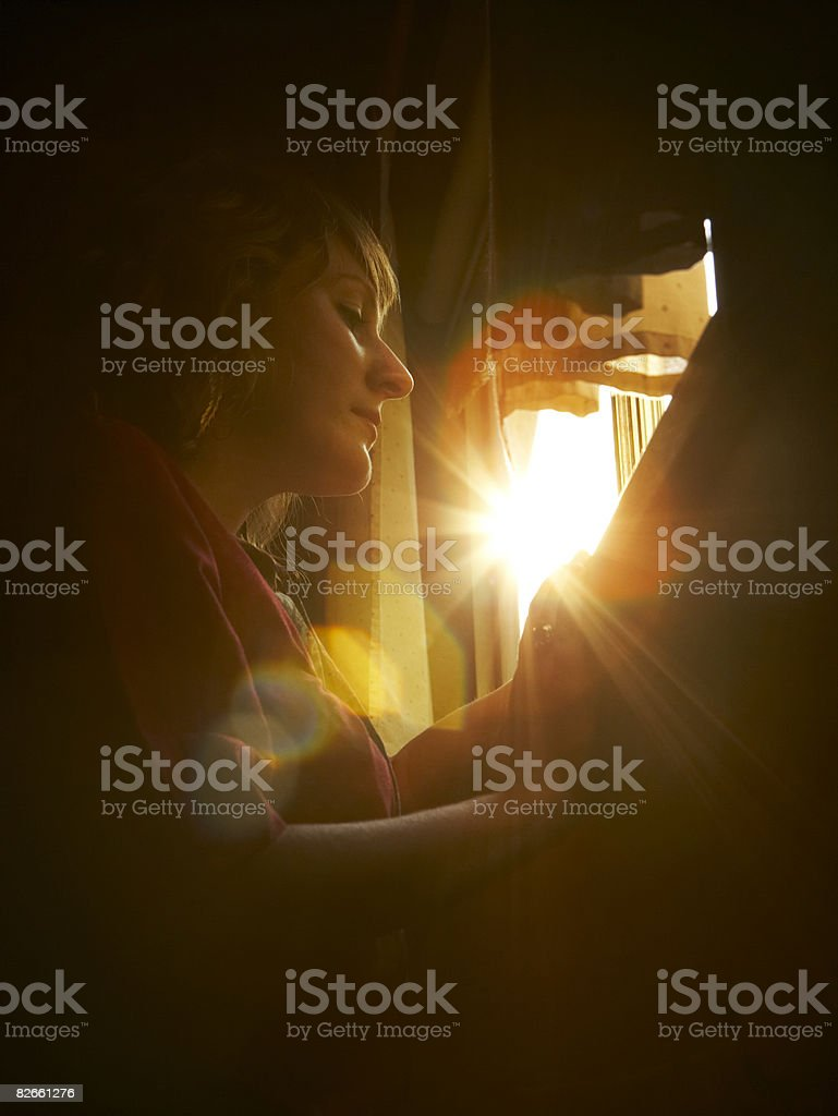 Flare through window as woman looks out royalty-free stock photo