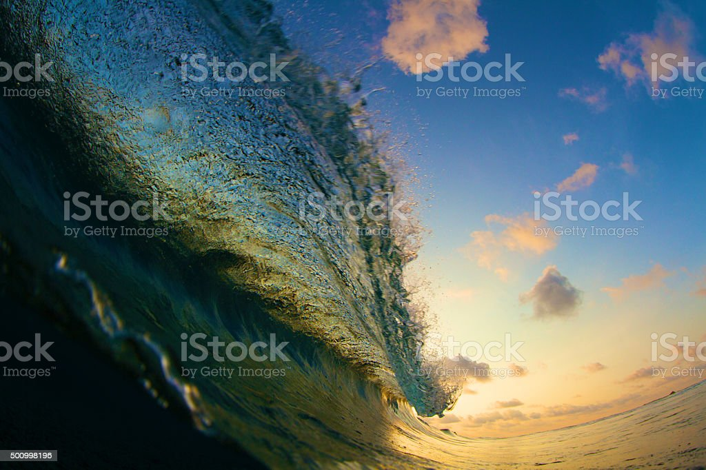 Flaring lip of a colorful breaking wave during sunset stock photo