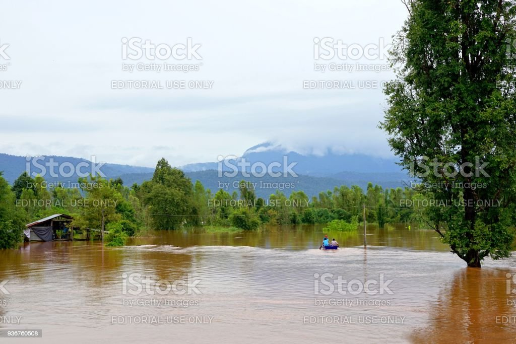 Flash flood by red turbid water flows down from the mountain due to torrential rain with people paddling boats. stock photo