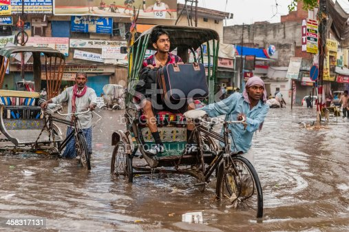 Varanasi, India - August 11, 2011: cycle rickshaws and a passenger with a suitcase try to make headway through a central street in Varanasi despite the heavy monsoon rain and the increasingly risky rising water level as a result of the flash flood.