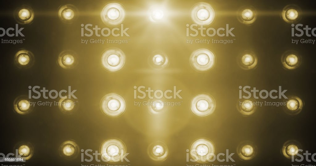 flashing shiny golden stage lights entertainment, spotlight projectors in the dark, gold warm soft light spotlight strike on black stock photo
