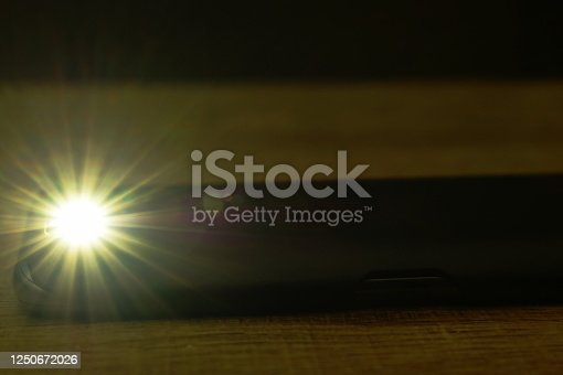 istock flashlight of mobile phone in dark night 1250672026
