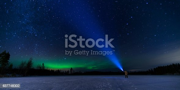 man puts blue flashlight to the sky in the middle of the frozen lake during the black night, with green lights away