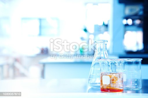 891126112istockphoto flask beaker with orange solution in science research education laboratory background 1033037610