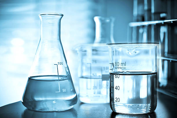 flask containing chemical liquid - beaker stock photos and pictures