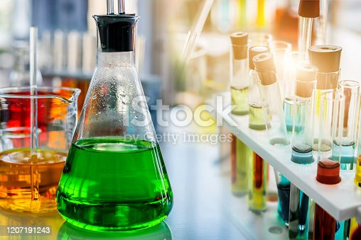 flask containing chemical liquid with test tube and lab glassware in chemical laboratory background, science laboratory research and development concept