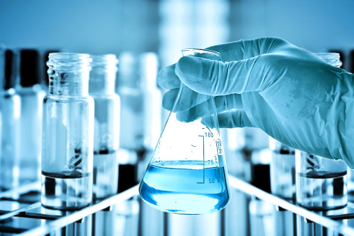 istock Flask in scientist hand and test tubes in rack 498015026