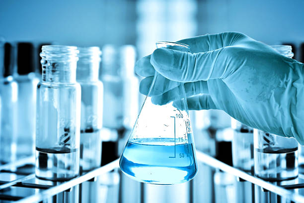 flask in scientist hand and test tubes in rack - laboratory equipment stock photos and pictures