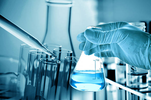 flask in scientist hand with laboratory background - flask stock photos and pictures