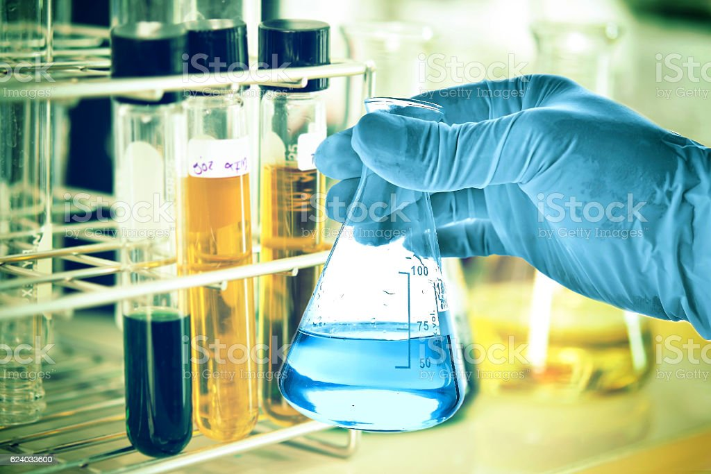 Flask in scientist hand with laboratory background stock photo