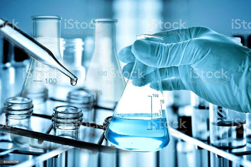 Flask in scientist hand with laboratory background royalty-free stock photo