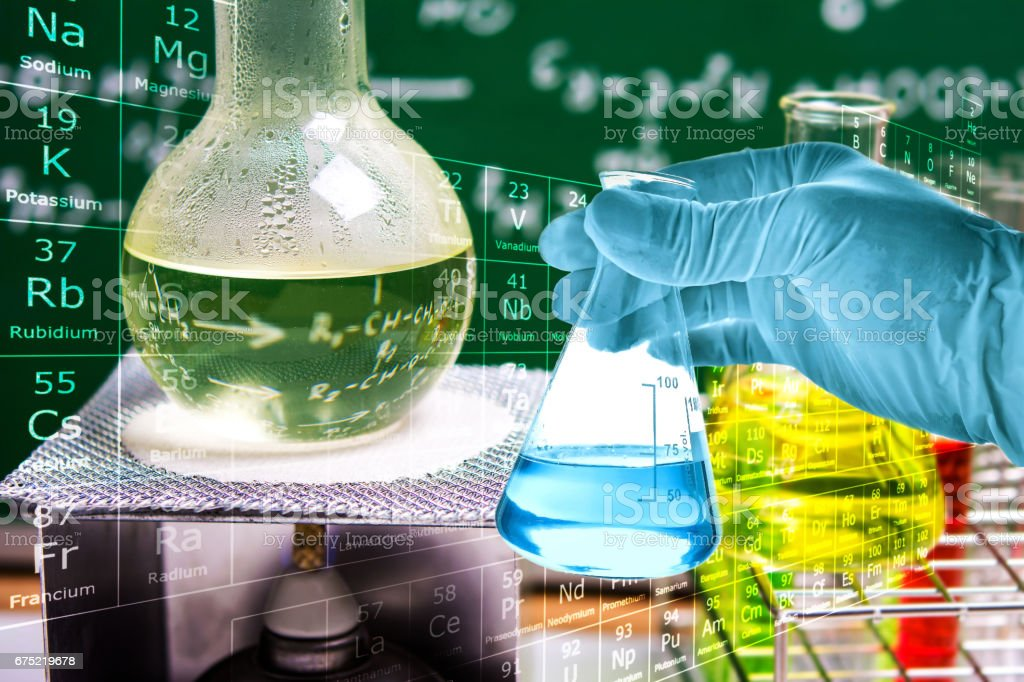 Flask in scientist hand with laboratory glassware background royalty-free stock photo