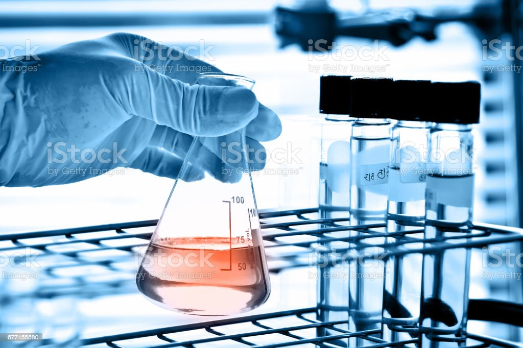 Flask in scientist hand with test tubes stock photo