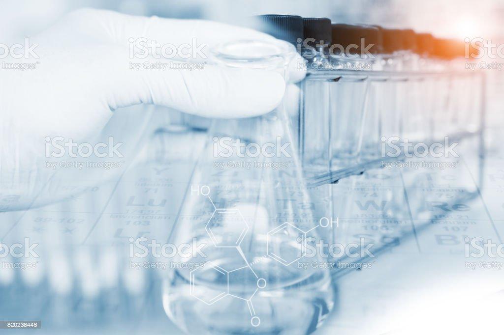 Matraz en científico mano con tubos de ensayo - foto de stock