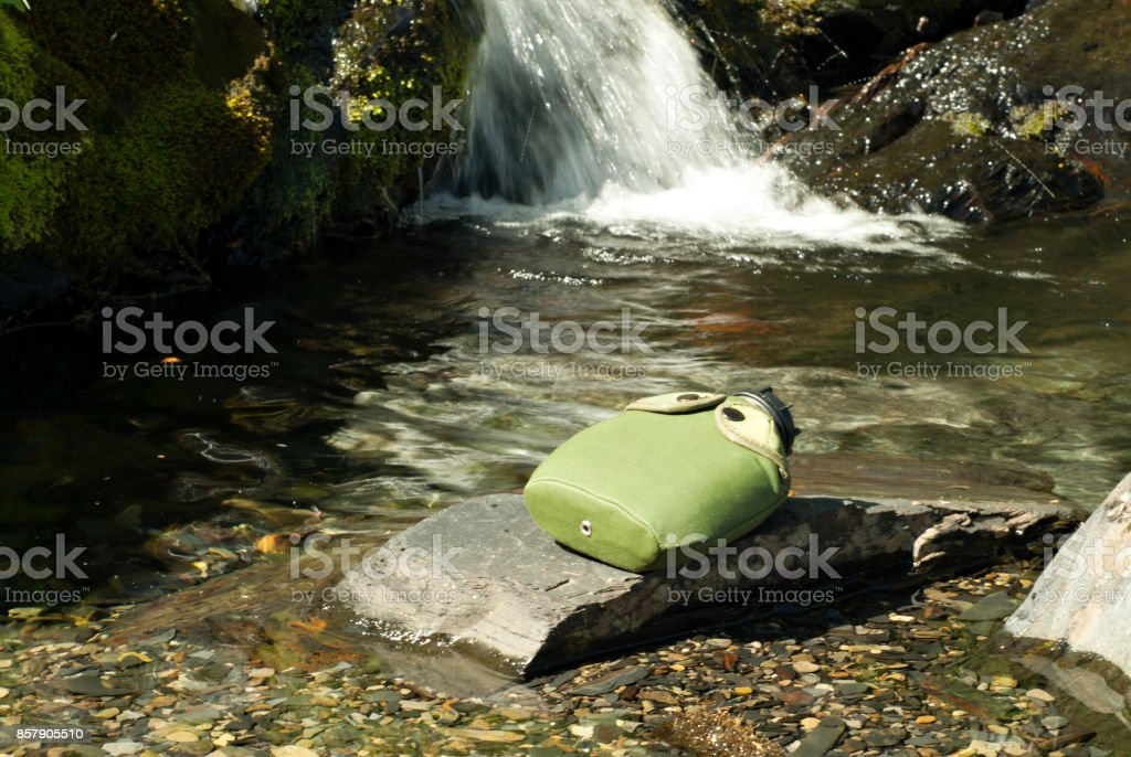 flask on a stone in front of a mountain stream stock photo