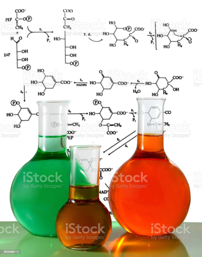 flasks against chemical formulas background close-up stock photo