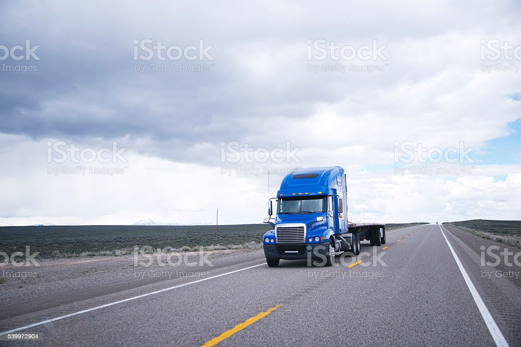 Flat bed semi-truck going to destination point for cargo stock photo