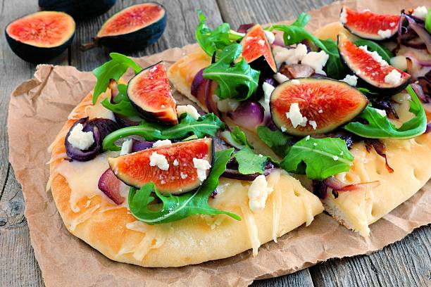 flat bread pizza with figs, arugula, goat cheese, over wood - feigen mit ziegenkäse stock-fotos und bilder