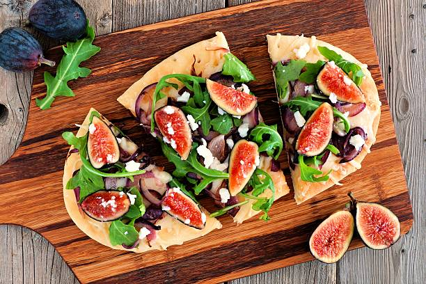 flat bread pizza with figs, arugula, goat cheese, overhead view - feigen mit ziegenkäse stock-fotos und bilder