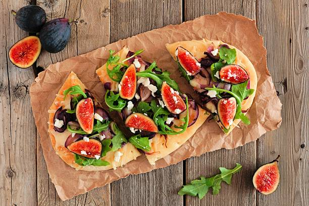 flat bread pizza with figs, arugula, overhead on rustic wood - feigen mit ziegenkäse stock-fotos und bilder