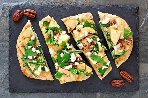 flat bread with apples, arugula, above view on slate server - fladenbrotpizza stock-fotos und bilder