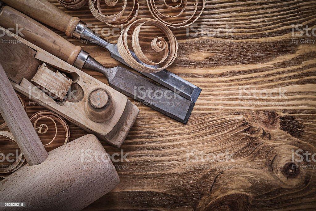 Flat chisels shaving plane curled shavings lump hammer on wooden stock photo