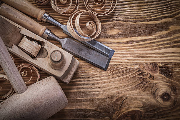 Flat chisels shaving plane curled shavings lump hammer on wooden Flat chisels shaving plane curled shavings lump hammer on wooden board construction concept. carving craft product stock pictures, royalty-free photos & images