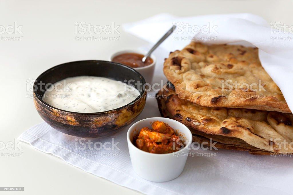 Flat Indian breads with raita and mango chutney stock photo