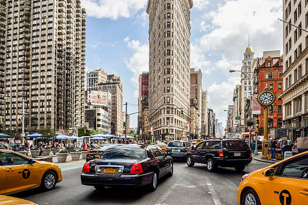 flat iron building with nyc fifth avenue and taxi cabs - flatiron gebäude stock-fotos und bilder