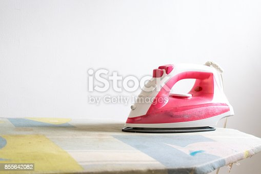 901620964 istock photo Flat iron, pink, on top of wooden ironing board, with scattered clothes and shirts on tops. 855642082