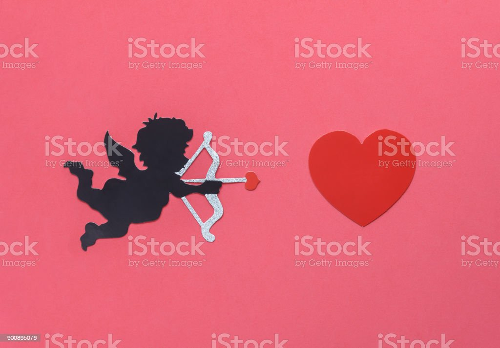 Flat lay aerial image of sign of valentines 's day background concept.DIY photo booth props the cupid shooting arrow to red heart on modern rustic pink wallpaper at home office desk studio.pastel tone stock photo
