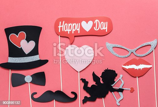 istock Flat lay aerial image of sign of valentines 's day background concept.DIY photo booth props the cupid shoot arrow to red heart on modern rustic pink wallpaper at home office desk studio.pastel tone. 900895132