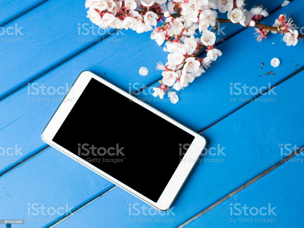 Flat Lay Almond Fruit Flowers And Digital Tablet On Blue Desk stock photo
