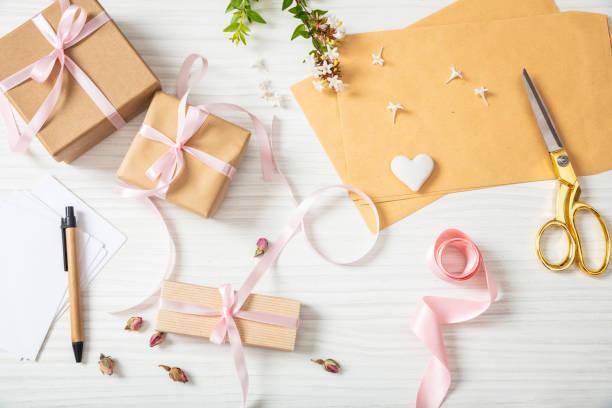 flach legen und top aussicht auf geschenk-boxen und einladungen auf einer weißen hölzernen tischplatte - geschenk zur taufe stock-fotos und bilder
