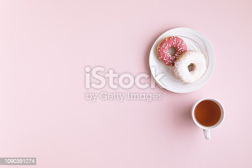 Flat lay and top view of office table desk. Workspace with laptop, donut, on pink background.
