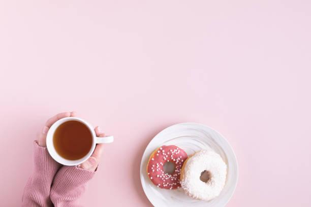 flach liegen und draufsicht der tisch schreibtisch. arbeitsbereich mit laptop, donut, auf rosa hintergrund. - rosen tee stock-fotos und bilder