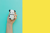 Flat lay antistress toy squish black white big panda squeezed in hand.Bright yellow blue background.Compressing, soft, squeezable items to relieve stress, problems, anxieties, worries.Summer concept.