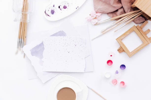 Flat lay art workspace, sheet of paper with paints and brushes on white table stock photo