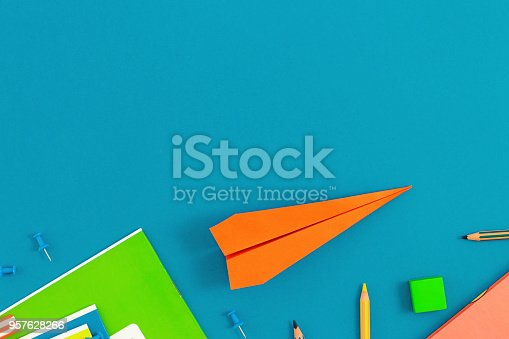 istock Flat lay back to school concept with paper airplane and school supplies on blue background. Top view school background 957628266
