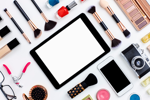 Flat lay beauty products surrounding digital tablet on white desk